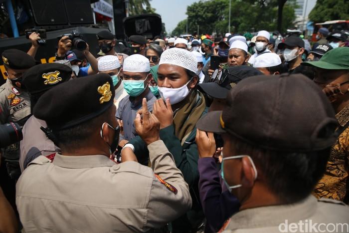 Polisi membubarkan dan menangkap para pendukung HRS yang berkerumun dan tidak mau membubarkan diri saat sidang berlangsung di PN Jakarta Timur, Jumat (26/3/2021).
