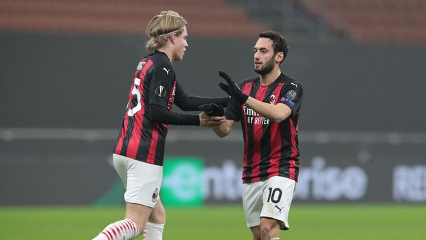 MILAN, ITALY - DECEMBER 03: Hakan Calhanoglu of A.C. Milan celebrates with Jens Petter Hauge after scoring their team's first goal during the UEFA Europa League Group H stage match between AC Milan and Celtic at San Siro Stadium on December 03, 2020 in Milan, Italy. Sporting stadiums around Italy remain under strict restrictions due to the Coronavirus Pandemic as Government social distancing laws prohibit fans inside venues resulting in games being played behind closed doors. (Photo by Emilio Andreoli/Getty Images)