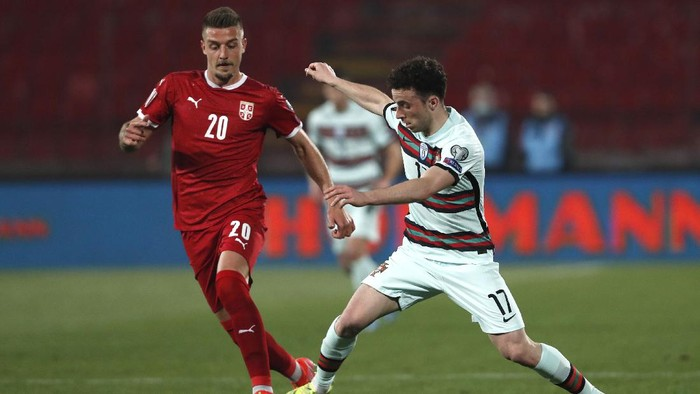 Serbias Sergej Milinkovic-Savic, left, and Portugals Diogo Jota challenge for the ball during the World Cup 2022 group A qualifying soccer match between Serbia and Portugal at the Rajko Mitic stadium in Belgrade, Serbia, Saturday, March 27, 2021. (AP Photo/Darko Vojinovic)