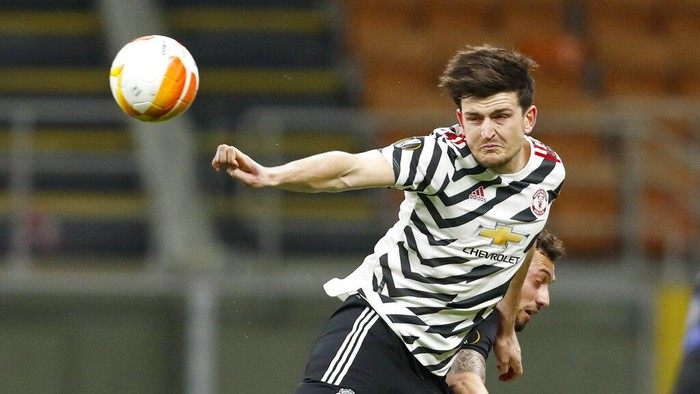 Manchester Uniteds Harry Maguire, left, heads the ball away from and AC Milans Hakan Calhanoglu during the Europa League round of 16 second leg soccer match between AC Milan and Manchester United at the San Siro Stadium, in Milan, Italy, Thursday, March 18, 2021. (AP Photo/Antonio Calanni)