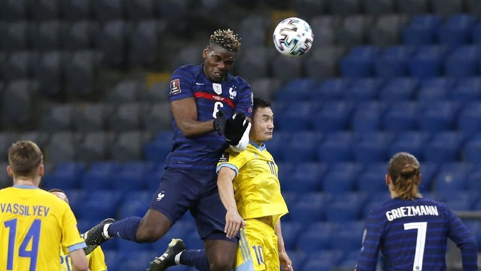 Frances Paul Pogba, center left, and Kazakhstans Serikzhan Muzhikov challenge for the ball during the World Cup 2022 group D qualifying soccer match between Kazakhstan and France at the Astana Arena stadium in Nur-Sultan, Kazakhstan, Sunday, March 28, 2021. (AP Photo/Stanislav Filippov)