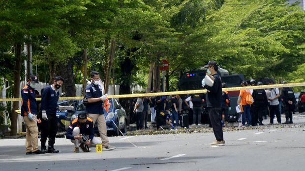 Petugas kepolisian melakukan pemeriksaan di sekitar sisa-sisa ledakan dugaan bom bunuh diri di depan Gereja Katolik Katedral, Makassar, Sulawesi Selatan, Minggu (28/3/2021). Ledakan bom di gereja tersebut mengakibatkan dua korban tewas yang diduga pelaku bom bunuh diri serta melukai 14 orang jemaat dan petugas gereja. ANTARA FOTO/Abriawan Abhe/foc.