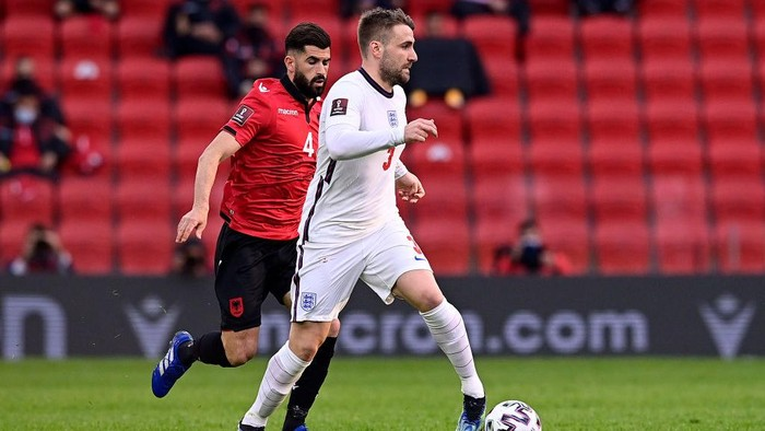 TIRANA, ALBANIA - MARCH 28: Luke Shaw of England runs with the ball whilst under pressure from Elseid Hysaj of Albania during the FIFA World Cup 2022 Qatar qualifying match between Albania and England at the Qemal Stafa Stadium on March 28, 2021 in Tirana, Albania. Sporting stadiums around Europe remain under strict restrictions due to the Coronavirus Pandemic as Government social distancing laws prohibit fans inside venues resulting in games being played behind closed doors.  (Photo by Mattia Ozbot/Getty Images)