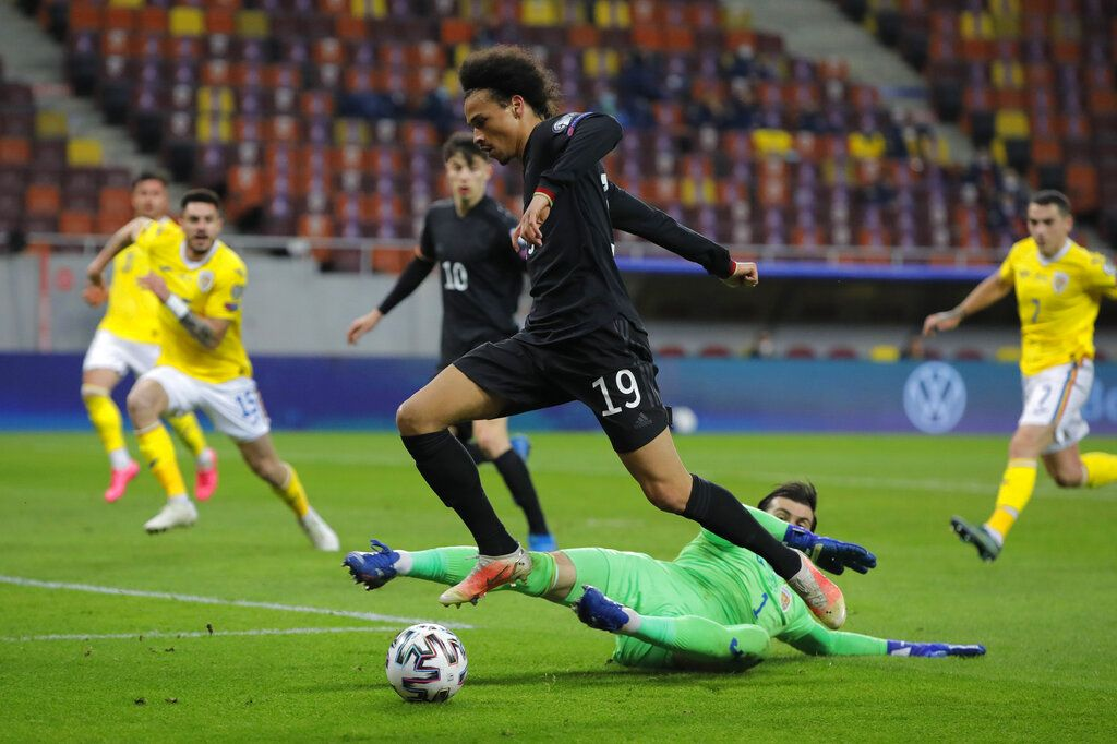Germany's Leroy Sane, top, vies or the ball with Romania goalkeeper Florin Nita during the World Cup 2022 group J qualifying soccer match between Romania and Germany at the National Arena stadium in Bucharest, Romania, Sunday, March 28, 2021. (AP Photo/Vadim Ghirda)