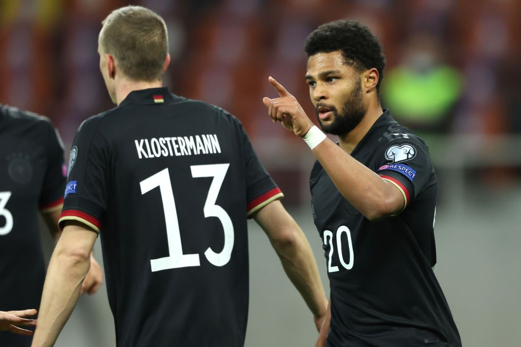 BUCHAREST, ROMANIA - MARCH 28: Serge Gnabry of Germany celebrates with team mate Lukas Klostermann after scoring their side's first goal during the FIFA World Cup 2022 Qatar qualifying match between Romania and Germany at the National Arena on March 28, 2021 in Bucharest, Romania. Sporting stadiums around Romania remain under strict restrictions due to the Coronavirus Pandemic as Government social distancing laws prohibit fans inside venues resulting in games being played behind closed doors.  (Photo by Alexander Hassenstein/Getty Images)