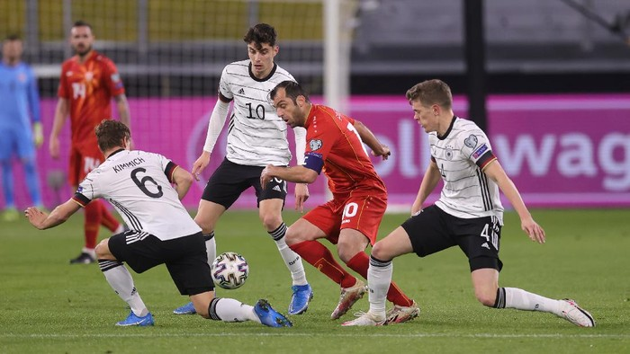 DUISBURG, GERMANY - MARCH 31: Goran Pandev of North Macedonia is challenged by Joshua Kimmich, Kai Havertz and Matthias Ginter of Germany  during the FIFA World Cup 2022 Qatar qualifying match between Germany and North Macedonia at Schauinsland-Reisen-Arena on March 31, 2021 in Duisburg, Germany. Sporting stadiums around Germany remain under strict restrictions due to the Coronavirus Pandemic as Government social distancing laws prohibit fans inside venues resulting in games being played behind closed doors. (Photo by Alex Grimm/Getty Images)