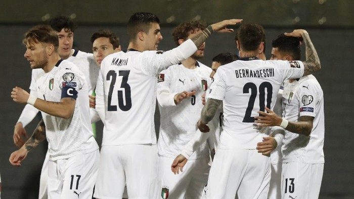 Italys Stefano Sensi, covered by his teammates, celebrates after scoring his sides opening goal during the World Cup 2022 Group C qualifying soccer match between Lithuania and Italy at LFF stadium in Vilnius, Wednesday, March 31, 2021. (AP Photo/Mindaugas Kulbis)