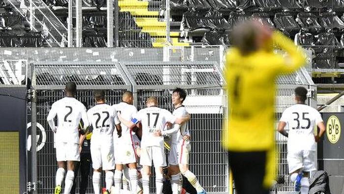 Frankfurts Andre Silva, background, celebrates after scoring during the German Bundesliga soccer match between Borussia Dortmund and Eintracht Frankfurt in Dortmund, Germany, Saturday, April 3, 2021. (AP Photo/Martin Meissner, Pool)