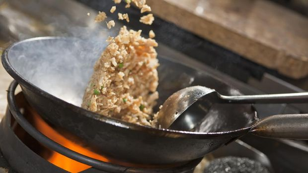 Closeup of fried rice being cooked in wok
