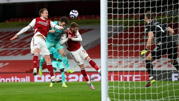 LONDON, ENGLAND - APRIL 03: Diogo Jota of Liverpool scores their teams first goal under pressure from Rob Holding and Calum Chambers of Arsenal during the Premier League match between Arsenal and Liverpool at Emirates Stadium on April 03, 2021 in London, England. Sporting stadiums around the UK remain under strict restrictions due to the Coronavirus Pandemic as Government social distancing laws prohibit fans inside venues resulting in games being played behind closed doors. (Photo by Catherine Ivill/Getty Images)