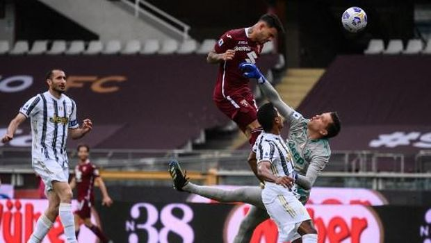 Torino's Paraguayan forward Antonio Sanabria (Top) shoots a header to score an equalizer past Juventus' Polish goalkeeper Wojciech Szczesny (R) during the Italian Serie A football match Torino vs Juventus on April 03, 2021 at the Olympic stadium in Turin. (Photo by Marco BERTORELLO / AFP)