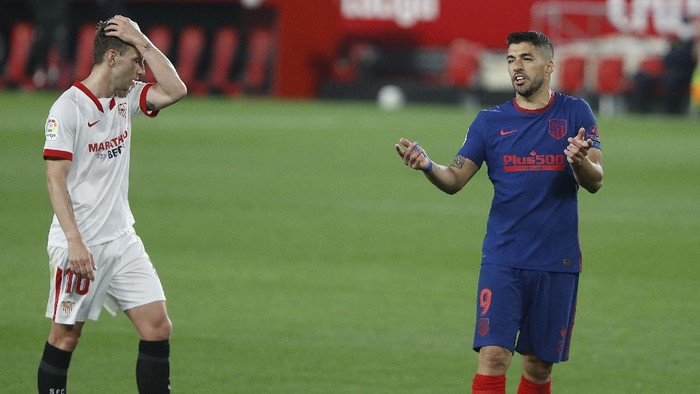 Atletico Madrids Luis Suarez, right, reacts during a Spanish La Liga soccer match between Sevilla and Atletico de Madrid at the Ramon Sanchez-Pizjuan stadium in Seville, Spain, Sunday, April 4, 2021. (AP Photo/Angel Fernandez)