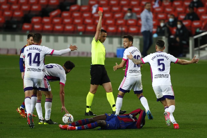 Referee Santiago Jaime Latre shows a red card to Valladolids Oscar Plano after he tackled Barcelonas Ousmane Dembele during the Spanish La Liga soccer match between FC Barcelona and Valladolid CF at the Camp Nou stadium in Barcelona, Spain, Monday, April 5, 2021. (AP Photo/Joan Monfort)
