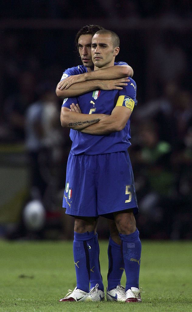 BERLIN - JULY 09:  Fabio Cannavaro (R) of Italy is hugged by teammate, Andrea Pirlo, as they watch the penalty shoot out during the FIFA World Cup Germany 2006 Final match between Italy and France at the Olympic Stadium on July 9, 2006 in Berlin, Germany.  (Photo by Ben Radford/Getty Images)