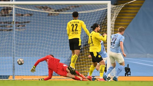 MANCHESTER, ENGLAND - APRIL 06: Kevin De Bruyne of Manchester City scores their team's first goal under pressure from Emre Can of Borussia Dortmund during the UEFA Champions League Quarter Final match between Manchester City and Borussia Dortmund at Manchester City Football Academy on April 06, 2021 in Manchester, England. Sporting stadiums around the UK remain under strict restrictions due to the Coronavirus Pandemic as Government social distancing laws prohibit fans inside venues resulting in games being played behind closed doors. (Photo by Michael Regan/Getty Images)