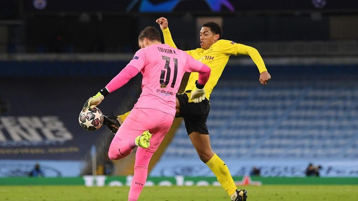 MANCHESTER, ENGLAND - APRIL 06: Jude Bellingham of Borussia Dortmund tackles Ederson of Manchester City to win the ball during the UEFA Champions League Quarter Final match between Manchester City and Borussia Dortmund at Etihad Stadium on April 06, 2021 in Manchester, England. Sporting stadiums around the UK remain under strict restrictions due to the Coronavirus Pandemic as Government social distancing laws prohibit fans inside venues resulting in games being played behind closed doors. (Photo by Michael Regan/Getty Images)