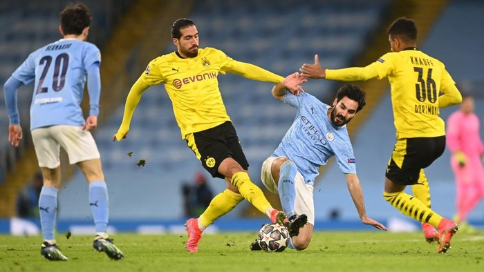 MANCHESTER, ENGLAND - APRIL 06: Emre Can and Ansgar Knauff of Borussia Dortmund battle for possession with Ilkay Guendogan of Manchester City during the UEFA Champions League Quarter Final match between Manchester City and Borussia Dortmund at Etihad Stadium on April 06, 2021 in Manchester, England. Sporting stadiums around the UK remain under strict restrictions due to the Coronavirus Pandemic as Government social distancing laws prohibit fans inside venues resulting in games being played behind closed doors. (Photo by Michael Regan/Getty Images)