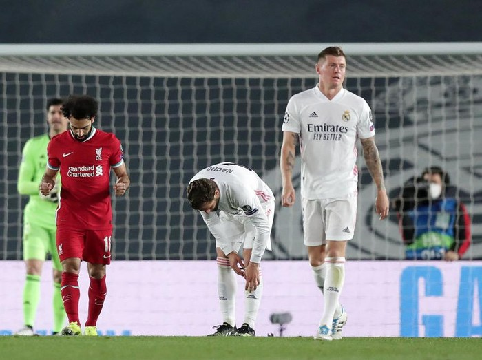 MADRID, SPAIN - APRIL 06: Mohamed Salah of Liverpool (L) celebrates after scoring his teams first goal as Toni Kroos of Real Madrid (R) look dejected during the UEFA Champions League Quarter Final match between Real Madrid and Liverpool FC at Estadio Alfredo Di Stefano on April 06, 2021 in Madrid, Spain. Sporting stadiums around Spain remain under strict restrictions due to the Coronavirus Pandemic as Government social distancing laws prohibit fans inside venues resulting in games being played behind closed doors. (Photo by Gonzalo Arroyo Moreno/Getty Images)
