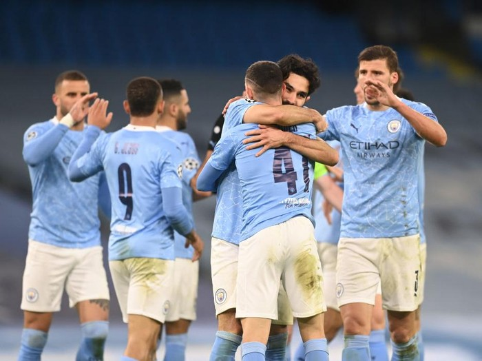 MANCHESTER, ENGLAND - APRIL 06: Phil Foden of Manchester City celebrates with teammate Ilkay Guendogan after scoring their teams second goal during the UEFA Champions League Quarter Final match between Manchester City and Borussia Dortmund at Manchester City Football Academy on April 06, 2021 in Manchester, England. Sporting stadiums around the UK remain under strict restrictions due to the Coronavirus Pandemic as Government social distancing laws prohibit fans inside venues resulting in games being played behind closed doors.  (Photo by Michael Regan/Getty Images)