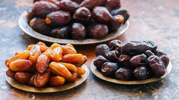 Various of dried dates or kurma in a vintage plates.