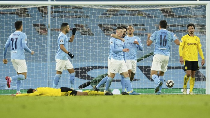 Manchester Citys Phil Foden celebrates after scoring his sides second goal during the Champions League, first leg, quarterfinal soccer match between Manchester City and Borussia Dortmund at the Etihad stadium in Manchester, Tuesday, April 6, 2021. (AP Photo/Dave Thompson)