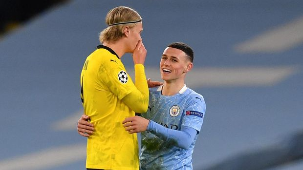 Manchester City's English midfielder Phil Foden (R) walks off the pitch with Dortmund's Norwegian forward Erling Braut Haaland after  the UEFA Champions League first leg quarter-final football match between Manchester City and Borussia Dortmund at the Etihad Stadium in Manchester, north west England, on April 6, 2021. (Photo by Paul ELLIS / AFP)