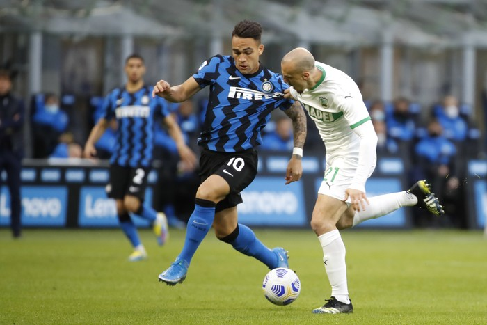 Inter Milans Lautaro Martinez, left, fights for the ball with Sassuolos Vlad Chiriches during the Serie A soccer match between Inter Milan and Sassuolo at the San Siro Stadium in Milan, Italy, Wednesday, April 7, 2021. (AP Photo/Antonio Calanni)