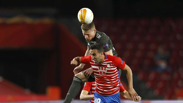 Manchester United's Scott McTominay, left, jumps for a header with Granada's Angel Montoro during the Europa League, quarterfinal, first leg soccer match between Granada and Manchester United at the Los Carmenes stadium in Granada, Spain, Thursday, April 8, 2021. (AP Photo/Fermin Rodriguez)