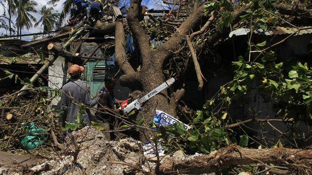 Sejumlah petugas memotong pohon yang tumbang menimpa salah satu rumah karena diterjang gelombang kencang akibat badai Siklon tropis Seroja di Kota Kupang, NTT, Kamis (8/4/2021). Badan Penanggulangan Bencana Daerah (BPBD) Kota Kupang mencatat sebanyak 1.264 rumah mengalami rusak berat, satu orang meninggal dunia dan tujuh orang luka berat dampak dari angin kencang pada Minggu (4/4). ANTARA FOTO/Kornellis Kaha/hp.