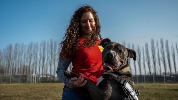 Xenia Katzurke, behavioral therapist for dogs at the Tierheim Berlin animal shelter, holds an American Staffordshire Terrier Mix called Marti, as she speaks to reporters on the grounds of the animal shelter in Berlin on February 23, 2021. - The sprawling complex in northeast Berlin, which houses domestic, as well as wild animals, was built in 2001, and counts as one of Europe's largest animal shelters. Germany has seen an explosion in pet adoption in the pandemic, with demand for cats, dogs and other furry companions soaring as people seek ways to ease loneliness and boredom. (Photo by John MACDOUGALL / AFP) / TO GO WITH AFP STORY BY FEMKE COLBORNE