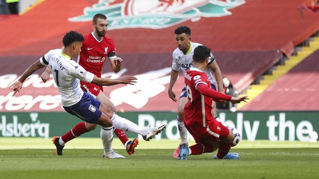 Aston Villa's Ollie Watkins, left, scores his side's opening goal during the English Premier League soccer match between Liverpool and Aston Villa at Anfield stadium in Liverpool, England, Saturday, April 10, 2021. (Clive Brunskill/Pool via AP)
