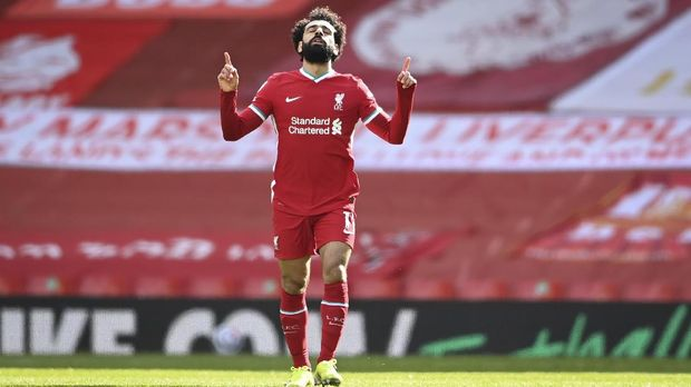 Liverpool's Mohamed Salah celebrates after scoring his side's opening goal during the English Premier League soccer match between Liverpool and Aston Villa at Anfield stadium in Liverpool, England, Saturday, April 10, 2021. (Laurence Griffiths/Pool via AP)