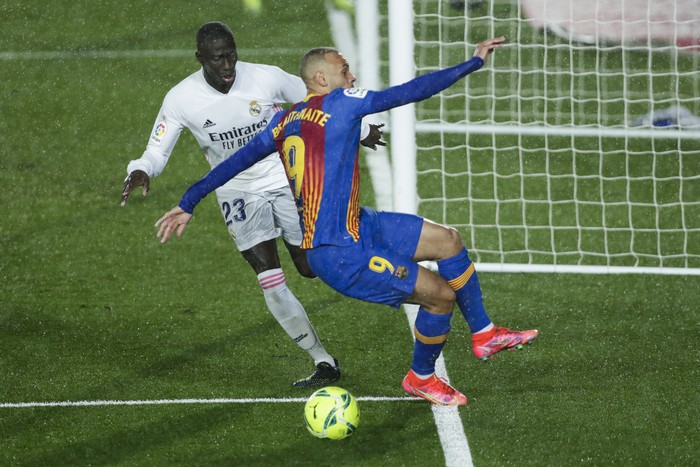 Barcelonas Martin Braithwaite, right, vies for the ball with Real Madrids Ferland Mendy during the Spanish La Liga soccer match between Real Madrid and FC Barcelona at the Alfredo di Stefano stadium in Madrid, Spain, Saturday, April 10, 2021. Real Madrid won 2-1. (AP Photo/Manu Fernandez)
