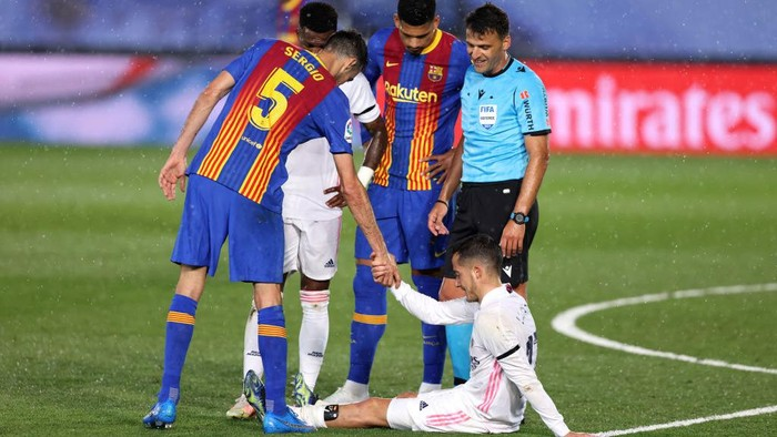 MADRID, SPAIN - APRIL 10: Lucas Vazquez of Real Madrid sits injured as Sergio Busquets of FC Barcelona offers his hand during the La Liga Santander match between Real Madrid and FC Barcelona at Estadio Alfredo Di Stefano on April 10, 2021 in Madrid, Spain. Sporting stadiums around Spain remain under strict restrictions due to the Coronavirus Pandemic as Government social distancing laws prohibit fans inside venues resulting in games being played behind closed doors.  (Photo by Angel Martinez/Getty Images)