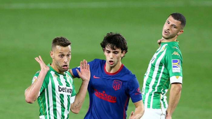 SEVILLE, SPAIN - APRIL 11: Joao Felix of Atletico de Madrid is challenged by Guido Rodriguez of Real Betis during the La Liga Santander match between Real Betis and Atletico de Madrid at Estadio Benito Villamarin on April 11, 2021 in Seville, Spain. Sporting stadiums around Spain remain under strict restrictions due to the Coronavirus Pandemic as Government social distancing laws prohibit fans inside venues resulting in games being played behind closed doors. (Photo by Fran Santiago/Getty Images)