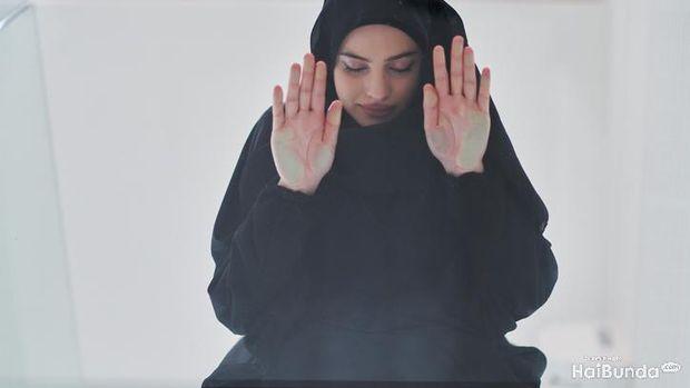 Young muslim woman doing sujud or sajdah on glass floor. Girl wearing black abaya praying salat to God during Ramadan