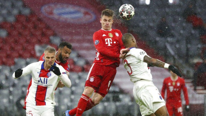 Bayerns Joshua Kimmich, left, and PSGs Presnel Kimpembe jump for the ball during the Champions League quarterfinal soccer match between Bayern Munich and Paris Saint Germain in Munich, Germany, Wednesday, April 7, 2021. (AP Photo/Matthias Schrader)