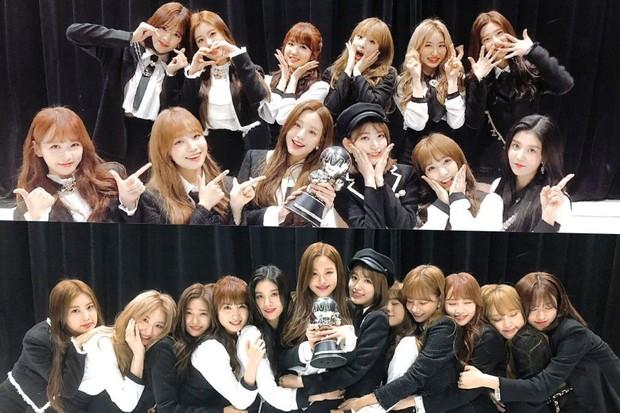 Potret para member IZ*ONE Memegang trophy kemenangan atas lagu mereka di acara musik.