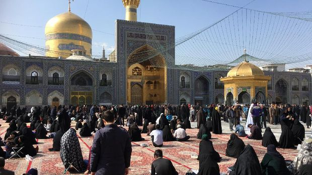 The big square of  the  Holy Shrine of Imam Reza with praying pilgrims in front of the mosque Mashad is the second biggest town in Iran.