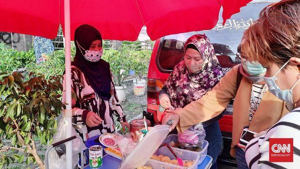 Sejumlah pedagang takjil sedang melayani pembeli di Jalan Bendungan Hilir (Benhil), Tanah Abang, Jakarta Pusat. Mereka mengeluhkan pengunjung yang sepi akibat bazar Pasar Benhil yang ditutup selama pandemi, Swlasa (14/3).