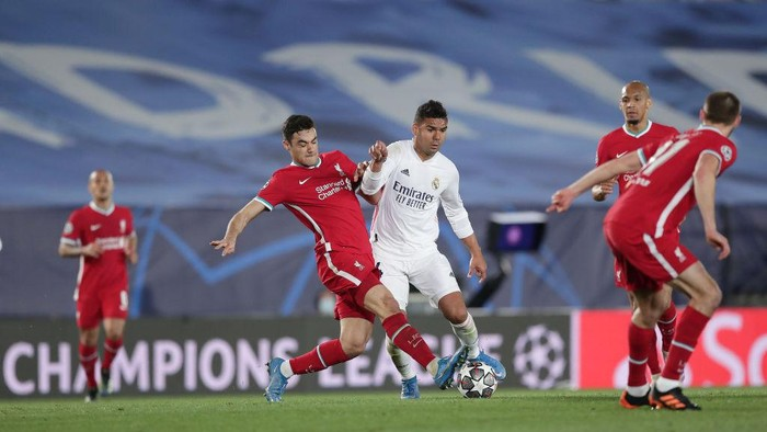 MADRID, SPAIN - APRIL 06: Carlos Casemiro (R) of Real Madrid CF competes for the ball with Ozan Kabak (L) of Liverpool FC during the UEFA Champions League Quarter Final match between Real Madrid and Liverpool FC at Estadio Alfredo Di Stefano on April 06, 2021 in Madrid, Spain. Sporting stadiums around Spain remain under strict restrictions due to the Coronavirus Pandemic as Government social distancing laws prohibit fans inside venues resulting in games being played behind closed doors. (Photo by Gonzalo Arroyo Moreno/Getty Images)