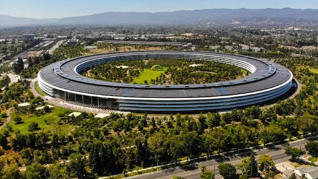Sunnyvale, California, USA - July 30, 2019: Cars driving past Apple Park, an iconic building located in Sunnyvale California. This image was taken on the morning of July 30, 2019. Apple Park serves as the international headquarters of Apple, Inc. The roof contains solar arrays that power the building.