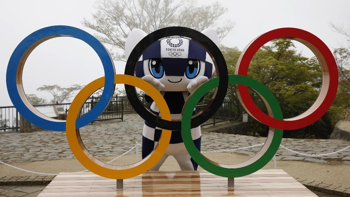 Tokyo 2020 Olympic Games mascot Miraitowa poses with a display of Olympic Symbol after an unveiling ceremony of the symbol on Mt. Takao in Hachioji, west of Tokyo, Wednesday, April 14, 2021, to mark 100 days before the start of the Olympic Games. (Kim Kyung-Hoon/Pool)