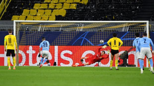 DORTMUND, GERMANY - APRIL 14: Riyad Mahrez of Manchester City scores their side's first goal past Marwin Hitz of Borussia Dortmund from the penalty spot during the UEFA Champions League Quarter Final Second Leg match between Borussia Dortmund and Manchester City at Signal Iduna Park on April 14, 2021 in Dortmund, Germany. Sporting stadiums around Germany remain under strict restrictions due to the Coronavirus Pandemic as Government social distancing laws prohibit fans inside venues resulting in games being played behind closed doors.  (Photo by Frederic Scheidemann/Getty Images)