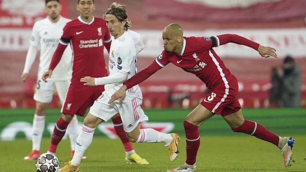 Real Madrid's Luka Modric, left, is challenged by Liverpool's Fabinho during a Champions League quarter final second leg soccer match between Liverpool and Real Madrid at Anfield stadium in Liverpool, England, Wednesday, April 14, 2021. (AP Photo/Jon Super)