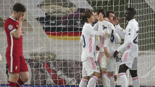 Liverpool's Diogo Jota, left, reacts as Real Madrid players celebrate at the end of the Champions League quarter final second leg soccer match between Liverpool and Real Madrid at Anfield stadium in Liverpool, England, Wednesday, April 14, 2021. (AP Photo/Jon Super)