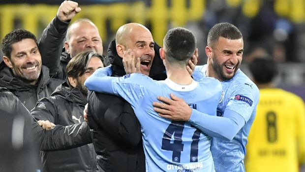 Manchester City's head coach Pep Guardiola celebrates with goal scorer Manchester City's Phil Foden during the Champions League quarterfinal second leg soccer match between Borussia Dortmund and Manchester City at the Signal Iduna Park stadium in Dortmund, Germany, Wednesday, April 14, 2021. (AP Photo/Martin Meissner, Pool)