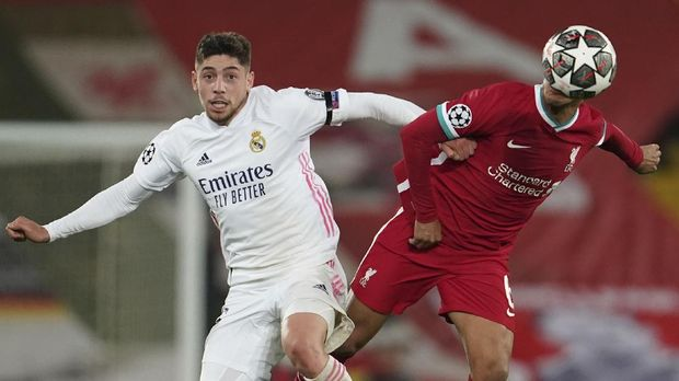 Liverpool's Thiago, right, is challenged by Real Madrid's Federico Valverde during a Champions League quarter final second leg soccer match between Liverpool and Real Madrid at Anfield stadium in Liverpool, England, Wednesday, April 14, 2021. (AP Photo/Jon Super)