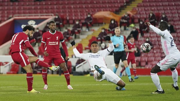 Liverpool's Mohamed Salah, left, attempts a shot at goal and misses in front of Real Madrid's Casemiro, center, and Real Madrid's Ferland Mendy, right, during a Champions League quarter final second leg soccer match between Liverpool and Real Madrid at Anfield stadium in Liverpool, England, Wednesday, April 14, 2021. (AP Photo/Jon Super)
