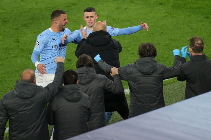 DORTMUND, GERMANY - APRIL 14: Phil Foden of Manchester City runs towards Pep Guardiola, Manager of Manchester City as he celebrates with team mate Kyle Walker after scoring their sides second goal during the UEFA Champions League Quarter Final Second Leg match between Borussia Dortmund and Manchester City at Signal Iduna Park on April 14, 2021 in Dortmund, Germany. Sporting stadiums around Germany remain under strict restrictions due to the Coronavirus Pandemic as Government social distancing laws prohibit fans inside venues resulting in games being played behind closed doors.  (Photo by Friedemann Vogel - Pool/Getty Images)